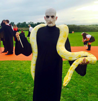 A guest dressed as Voldemort at an outdoor function holding a large albino burmese python